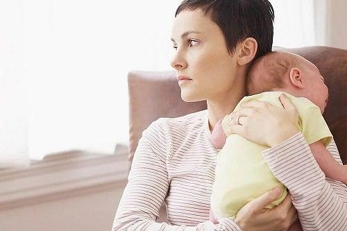Mamă tristă cu copilul în brațe