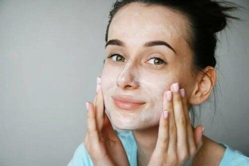 Fată care își aplică o cremă pe față