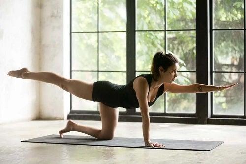 Femeie care face exercițiul pasăre-câine