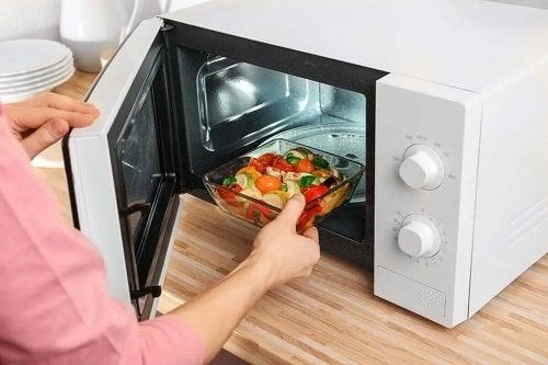 Persoană care evită plasticul în cuptorul cu microunde