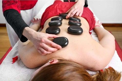 Terapeut care practică masajul cu pietre fierbinți