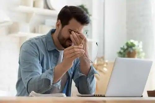 Bărbat obosit stând la PC