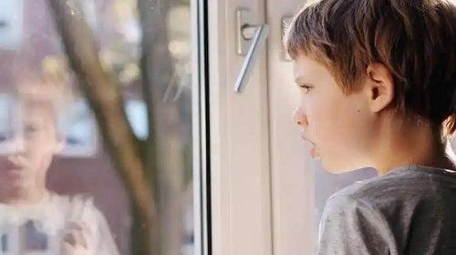 Copil autist uitându-se pe geam