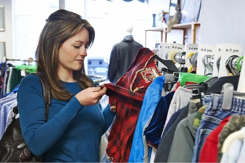 Femeie care cumpără haine second hand