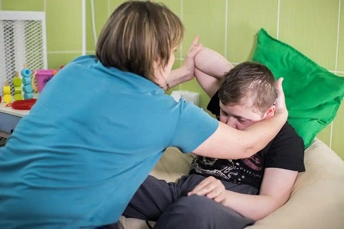 Asistentă care ajută un pacient cu paralizie cerebrală