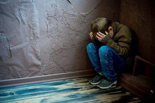 Copil abuzat stând într-un colț