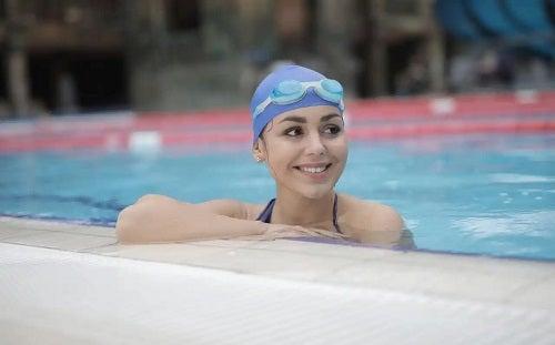 Fată care face antrenamentul cardiovascular cu impact redus în piscină
