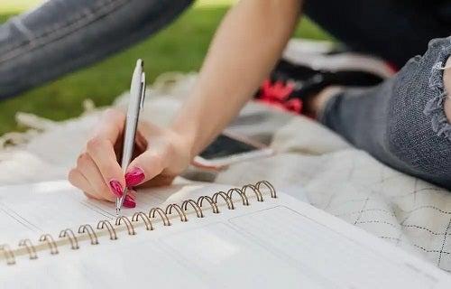Fată care scrie în jurnal