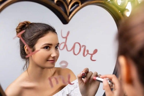 Fată care privește cu dragoste în oglindă