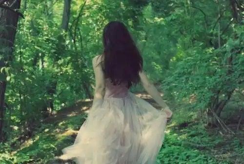 Fată care merge prin pădure