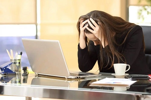 Femeie care nu controlează anxietatea la serviciu