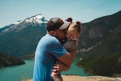 Tată care își ține în brațe copilul