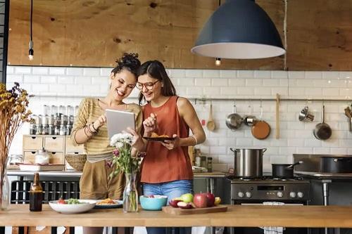 Femei care prepară o rețetă de sparanghel și cartofi gratinați